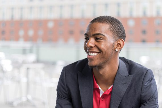 Marquel Thompson, photographed in profile, sits in front of a window and smiles broadly.