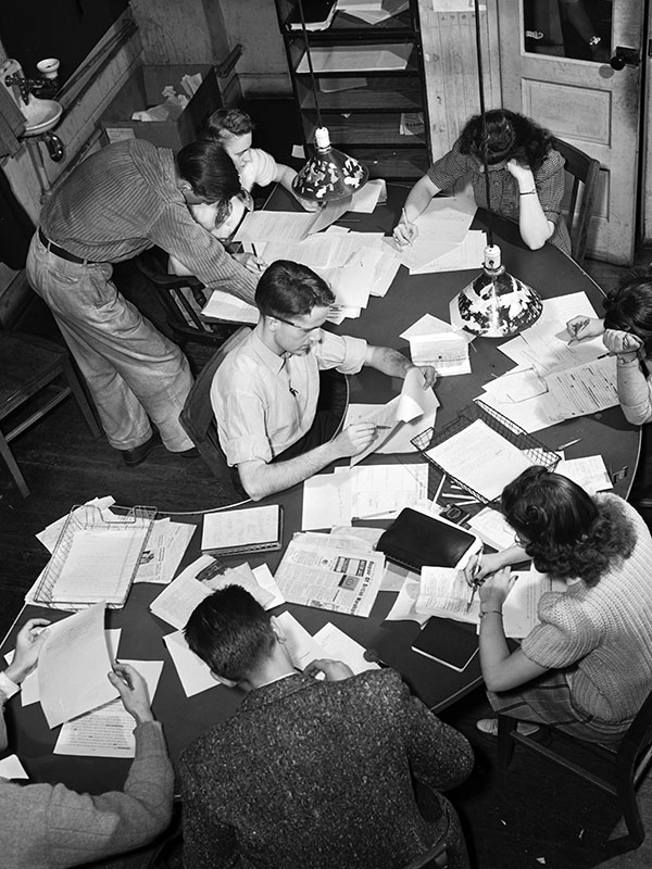 A black-and-white photo shows students huddled over a crescent shaped table, engrossed in their work, papers strewn about everywhere.