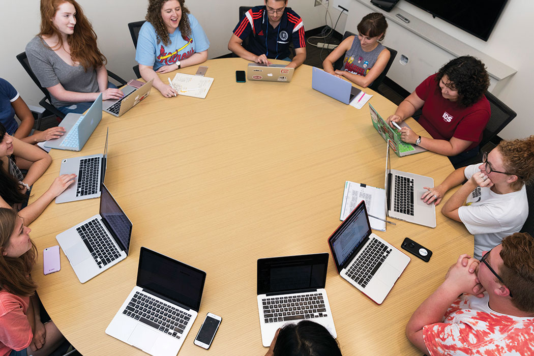 A full-color photo shows students gathered around a table, a laptop (and sometimes also a smartphone) in front of each of them.