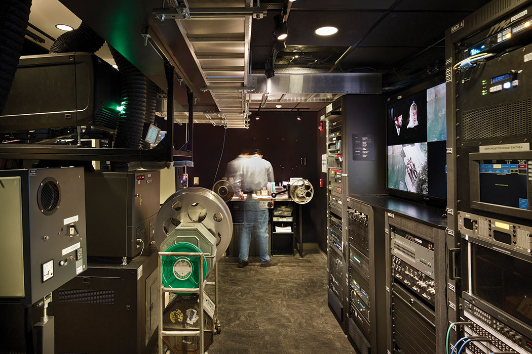 A person, blurred in movement, works in the projection booth of the IU Cinema. Brightly lit, the booth features wall-to-wall, floor-to-ceiling technology, including two film projectors to accommodate both 35mm and 16mm film reels, as well as two digital projectors and a touchscreen computer to orchestrate each cinematic event.