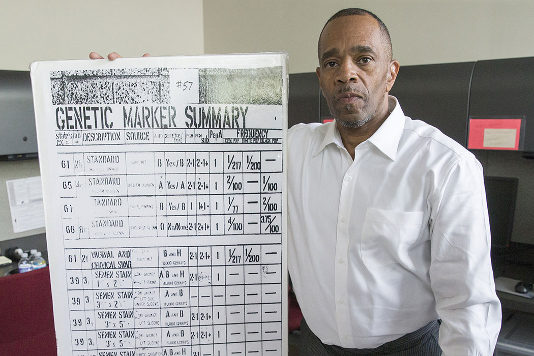 """Pinkins, in a crisp, white button-up shirt, holds a poster-size enlargement of a black-and-white report. It says """"Genetic Marker Summary"""" and has several rows and columns marked with numbers and labels."""