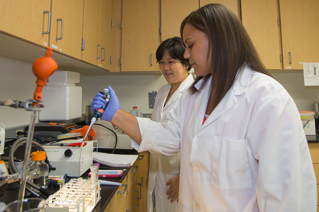 Kortany Baker, wearing a white lab coat and blue rubber gloves, uses scientific equipment to test bacterial solutions. Hisako Masuda, also in a white lab coat, oversees.