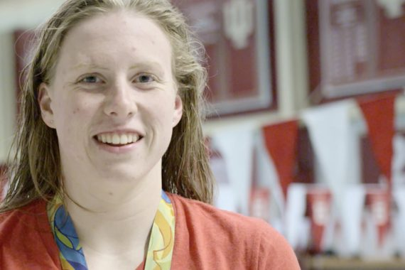 Lilly King, wearing an Olympic gold medal around her neck, smiles. She stands in front of a blurred background of banners touting the many accomplishments of IU Swimming and Diving over the years.