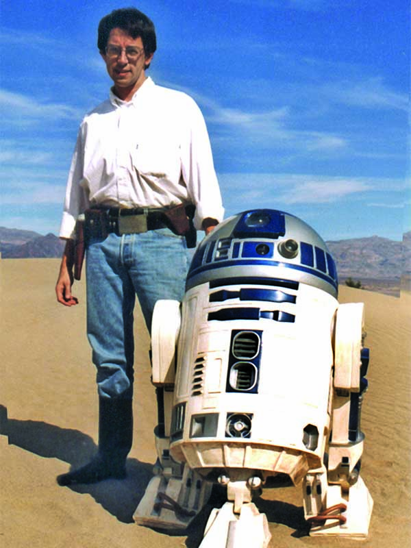 David West Reynolds standing in desert with Star Wars character R2D2