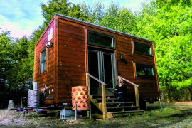 Laura Yates sitting on the steps of her tiny house, The Little Leaf.