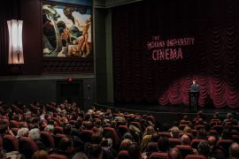 "A man in a dark suit stands before a full, seated audience. He stands at a podium on an elevated stage, lit by a spotlight in a dimly lit theatre. Behind him, the words ""The Indiana University Cinema"" is projected on the richly hued, velvet curtains that are gathered in luxurious folds."
