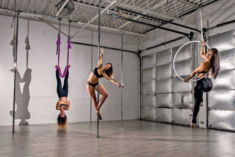 Anita DeCastro (center), BA'09, MA'14, owner of Wild Orchid Aerial Fitness and Dance, with Virginia Hojas (left) and Grace Wang (right) demonstrate aerial arts. Photo by Marc Lebryk.