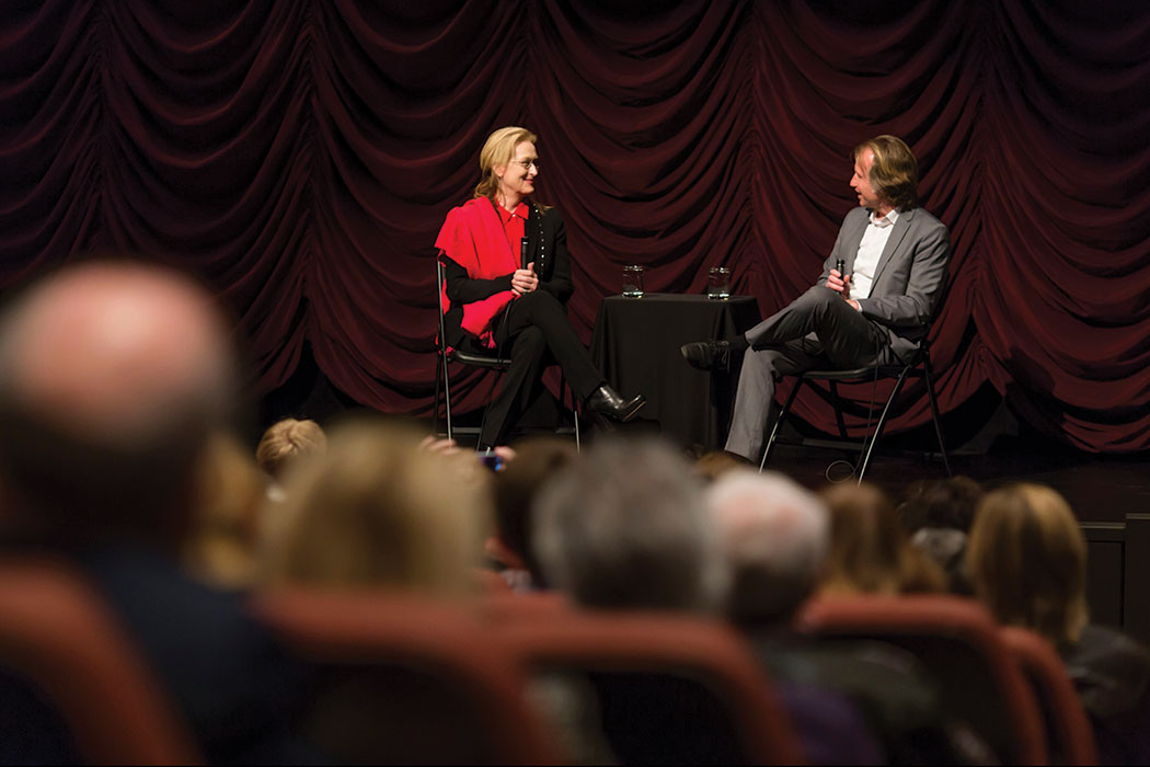 Academy Award-winning actress Meryl Streep, wearing a bright red scarf over an all-black outfit, sits on the IU Cinema stage, talking with IU Cinema Founding Director Jon Vickers, who wears a gray suit. The talk was part of Streep's 2014 visit to Bloomington, where she took part in the Jorgensen Guest Filmmaker Series, among other activities.