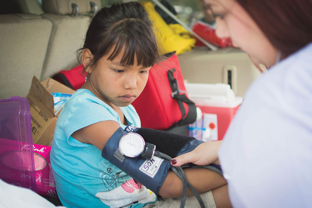 A nursing student tests a child's blood pressure at Pine Ridge.