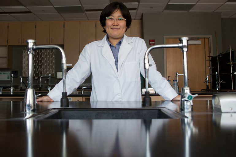 Hisako Masuda, wearing a white lab coat, stands in a chemistry lab behind a large, shiny black work table outfitted with silver instruments.
