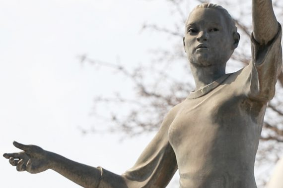 Faded bronze sculpture of a young woman with arms outstretched reaching for the sky with a clear sky in the background.