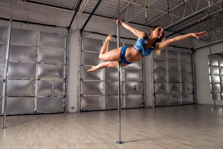 Anita DeCastro, BA'09, MA'14, demonstrates the superwoman pose on the pole. Sometimes called pole dancing, pole fitness, or pole acrobatics, this aerial art combines dance and acrobatics on a vertical pole. Photo by Marc Lebryk.