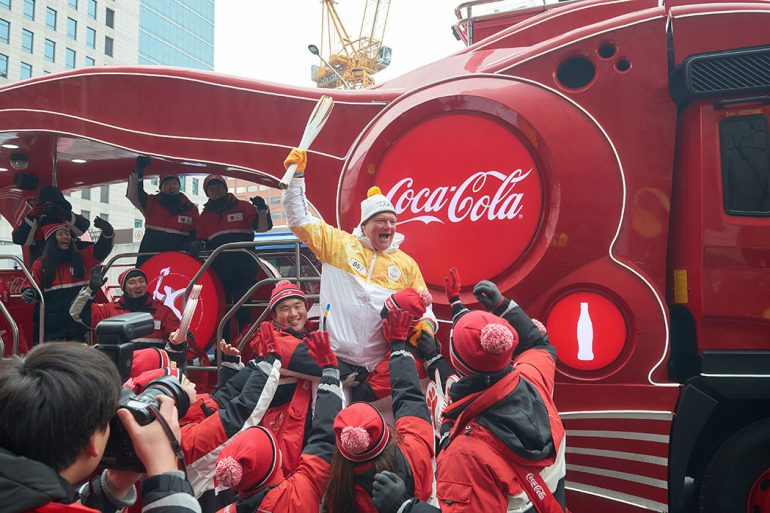 Supporters from Coca-Cola lift Ferguson into the air with the Olympic flame.