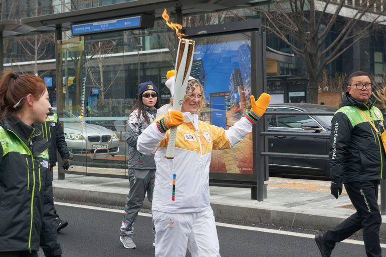 Kesner carries the Olympic flame for her leg of the 1,253-mile route through South Korea.