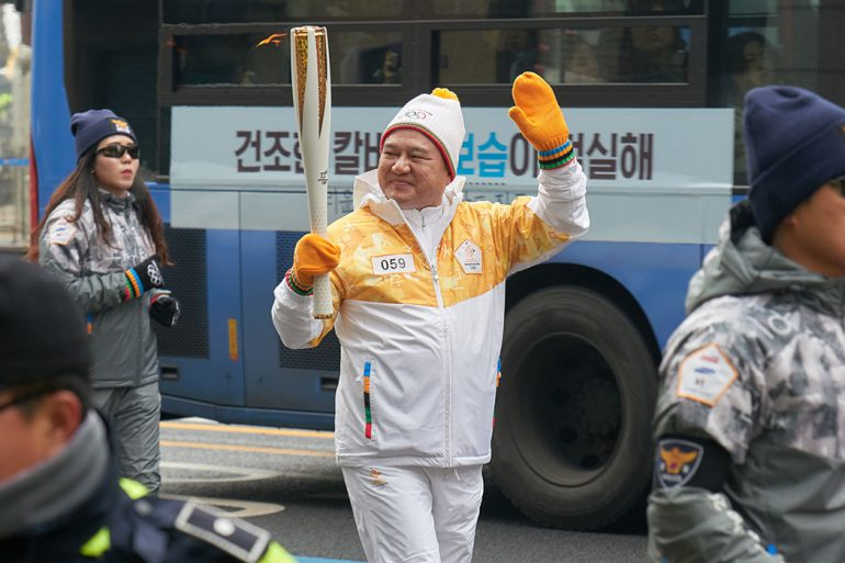 Young-Jin Kim, IU alumnus and chairman/CEO of Handok Inc., carries the torch for his leg of the relay.