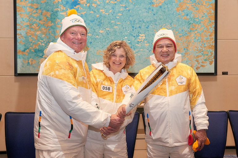 """IU alums Curtis A. Ferguson, Idalene """"Idie"""" Kesner (Kelley School of Business dean), and Young-Jin Kim pose with the torch."""