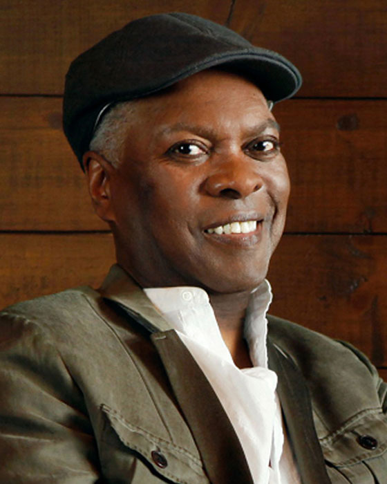 Booker T. Jones, wearing a white button-up shirt, green jacket, and black newsboy-style cap, smiles at the camera.