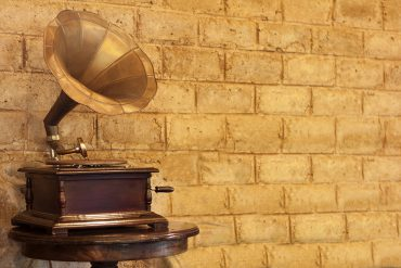 Gold gramophone in front of a golden-yellow brick wall.