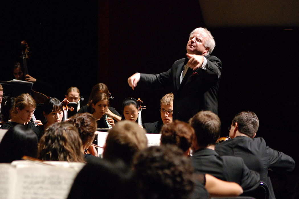 With eyes closed and arms outstretched, Leonard Slatkin stands on a raised platform conducting an orchestra.