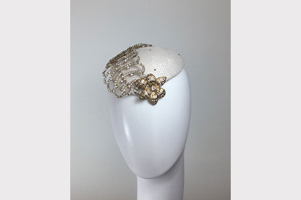 A rhinestone flower with a decorative crystal feather on top of a beret.