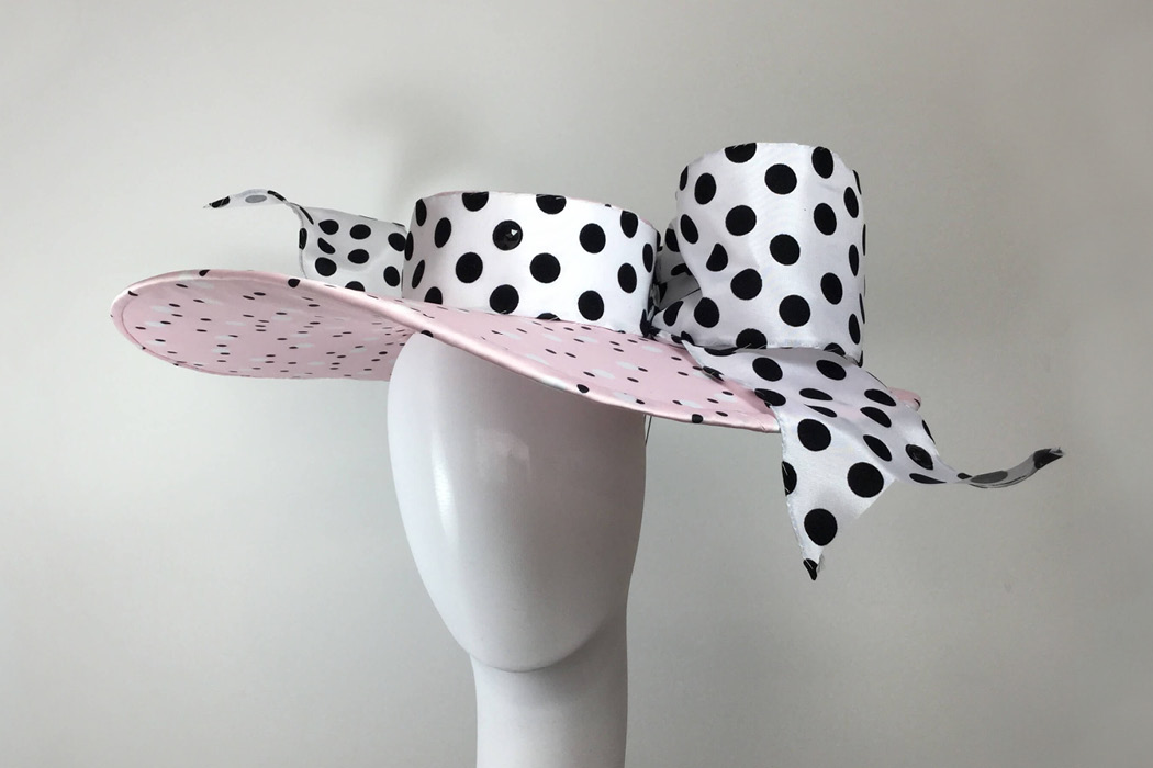 A wide-brimmed polka dot hat featuring a bow.