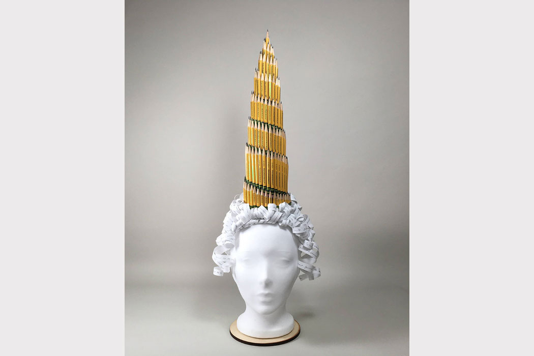 A tall hat made of #2 pencils sitting on top of a curly wig made of paper.