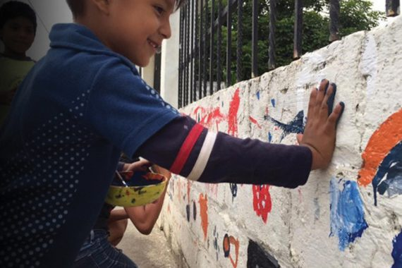 A smiling boy presses his paint-covered palm against a stone wall to mark his hand print.
