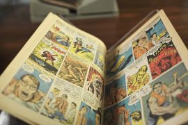 This image features the first comic book appearance of The Incredible Hulk. The comic is opened across a book rest.