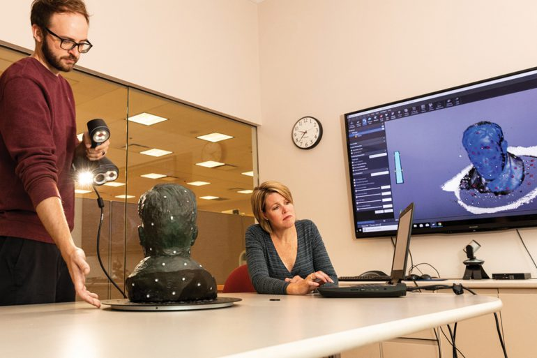 Miller and Johnson sit at a large table. While Johnson looks at the screen of a laptop, Miller holds a scanner pointed at a bust.