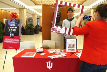 A student stands in front of a bust of Herman B Wells. The student holds a large picture frame with cream and crimson stripes. A woman in a red blazer snaps his picture.