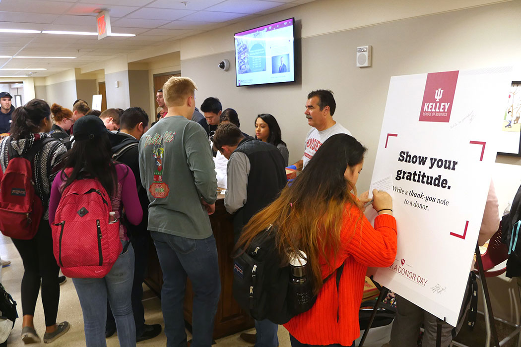 "Students crowd around a table to sign thank you cards to Kelley School of Business donors. In the foreground, a woman in a bright red sweater is writing a note on a large sign that reads: ""Show your gratitude. Write a thank-you note to a donor."""