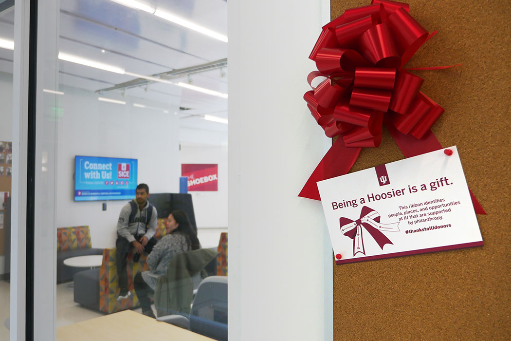 "Through a glass wall, we see students sitting in a large, brightly lit room identified as ""The Shoebox."" Outside the room, there is a shiny red bow and a card below it that reads: ""Being a Hoosier is a gift. This ribbon identifies people, places, and opportunities at IU that are supported by philanthropy. #thankstoIUdonors."""