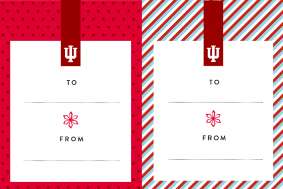 Two horizontal gift tags next to each other. Both tags feature a bold crimson tab with a white IU trident at the top, and a red snowflake on a white background with blank To and From lines in the center. The tag on the left features a border of light crimson with dark crimson polka dots. The tag on the right features a border of diagonal white, dark crimson, and aqua stripes.
