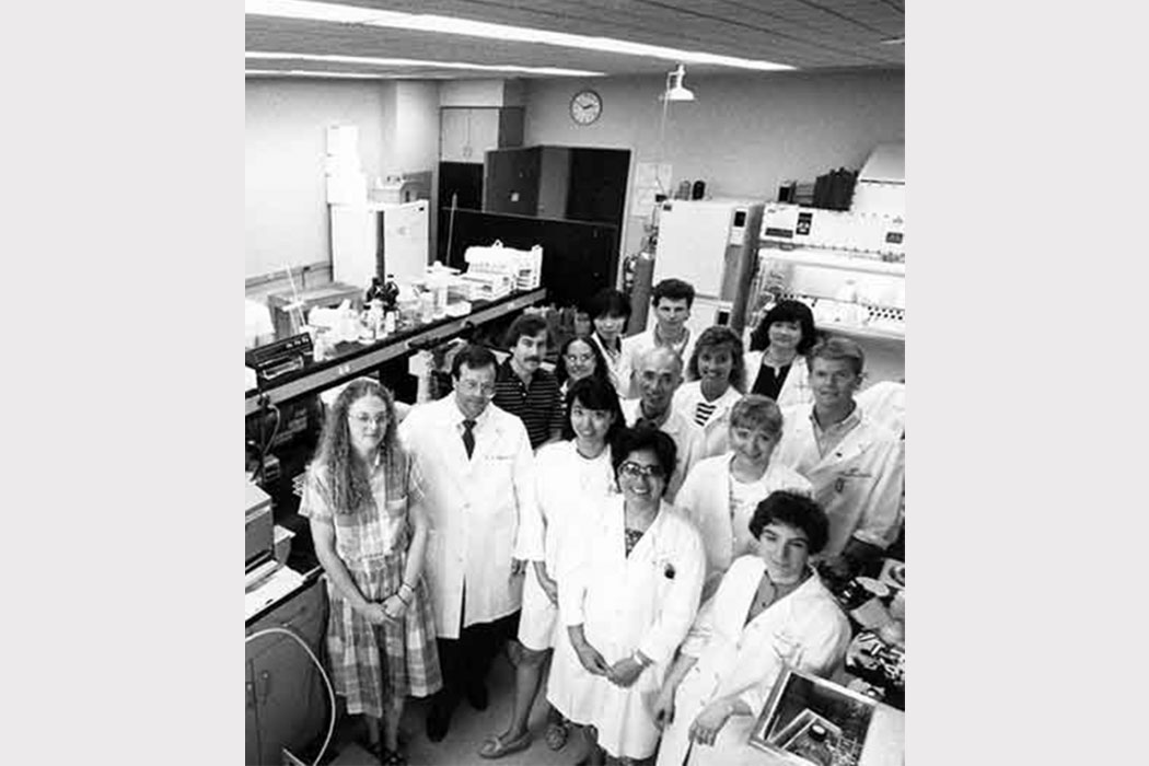 A retro black-and-white photo showing a group of people in a lab, smiling at the camera. Some of them wear white lab coats.
