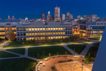 A night shot of the IUPUI campus shows the windows aglow against the backdrop of the Indianapolis skyline.