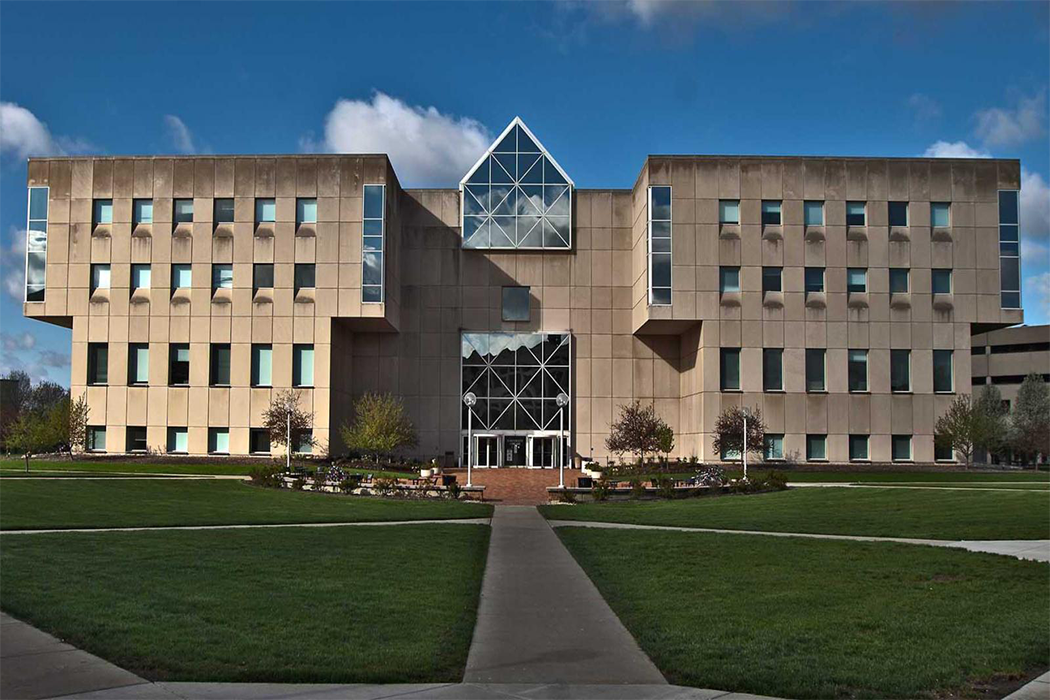 The University Library stands at the endpoint of several walkways separated by wide patches of green grass. The building is made of light stone and features many windows on its facade, including an expansive glass wall spanning several floors at its center.