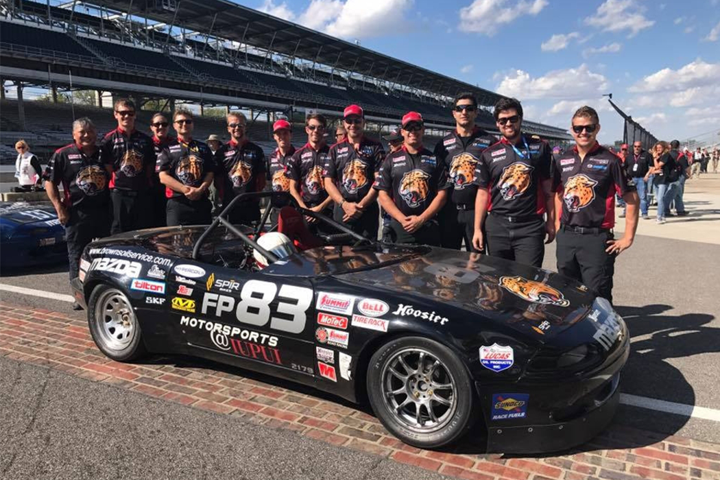 A group of people wearing matching black shirts with the IUPUI Jaguars logo stand behind a black race car at the Indianapolis Motor Speedway.