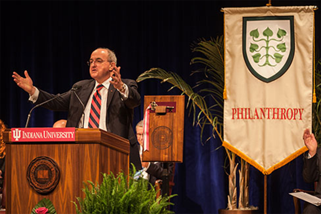 "Michael McRobbie speaks from behind a podium; Behind him hangs a large banner with the word ""Philanthropy"" and a crest of interlocking leaves on it."