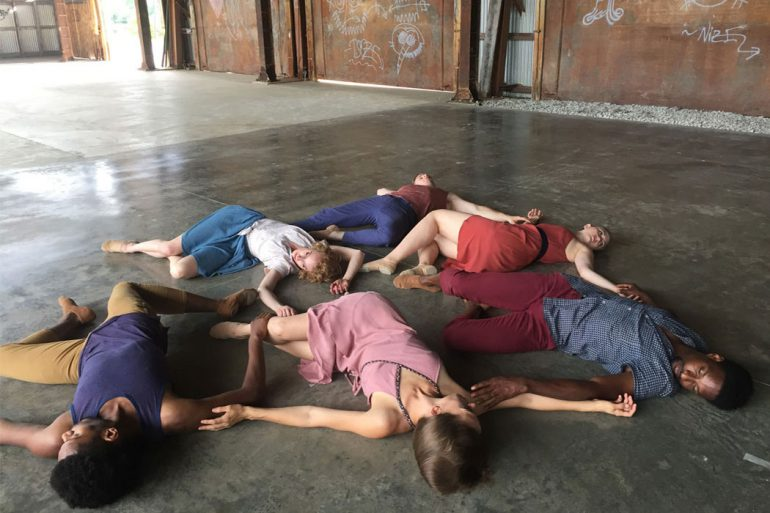 A group of dancers lie in a circle on the floor of the mill