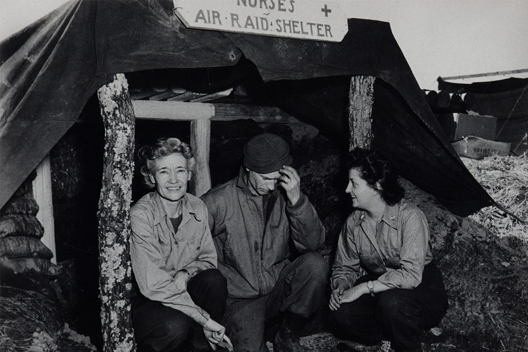Pyle and two nurses crouch in an entrenched air raid shelter in this black-and-white photo.