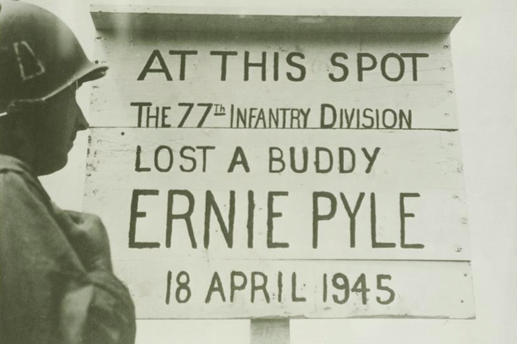 "Black-and-white photo of a soldier reading a makeshift memorial for Ernie Pyle that reads, ""At this spot the 77th infantry division lost a buddy: Ernie Pyle, 18 April 1945."""