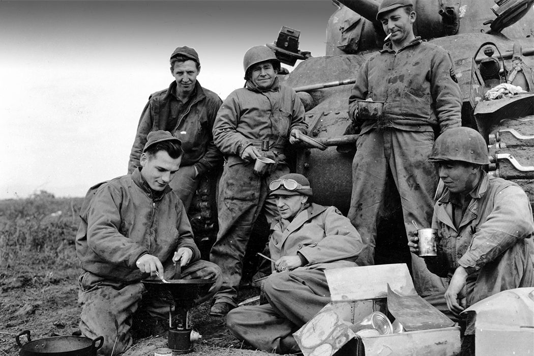 Black-and-white photo of Pyle and a group of soldiers relaxing in front of a tank while heating field rations in a skillet.