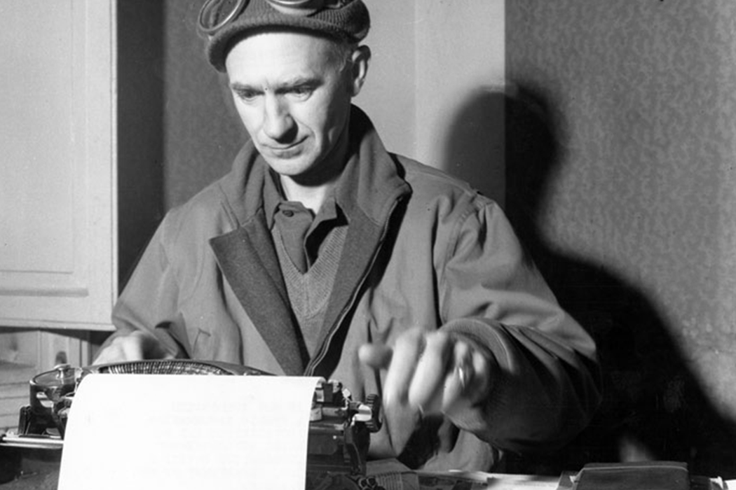 Black-and-white photo of Ernie Pyle writing at his typewriter.
