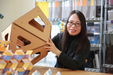 Jangmei Wu holds a section of an origami installation