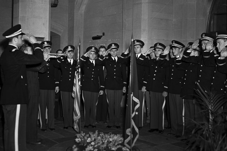 Uniformed service members salute the Memorial Circle Plaque and flags in this black-and-white photo taken circa 1939.