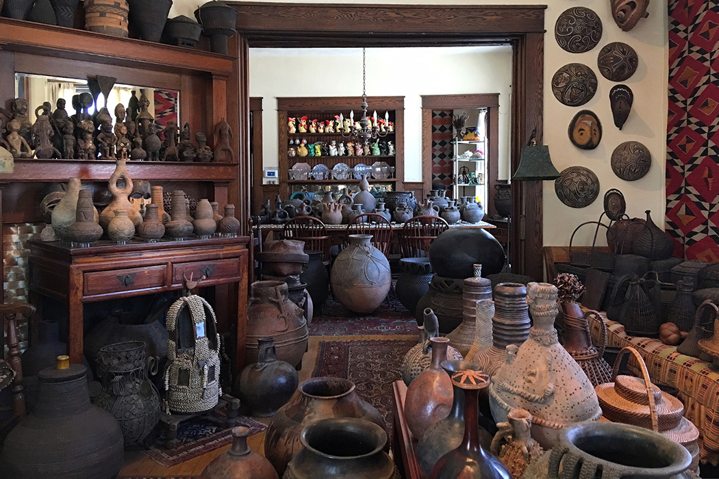 Hundreds of ethnographic objects—filling nearly every wall and flat surface—are displayed in a home.
