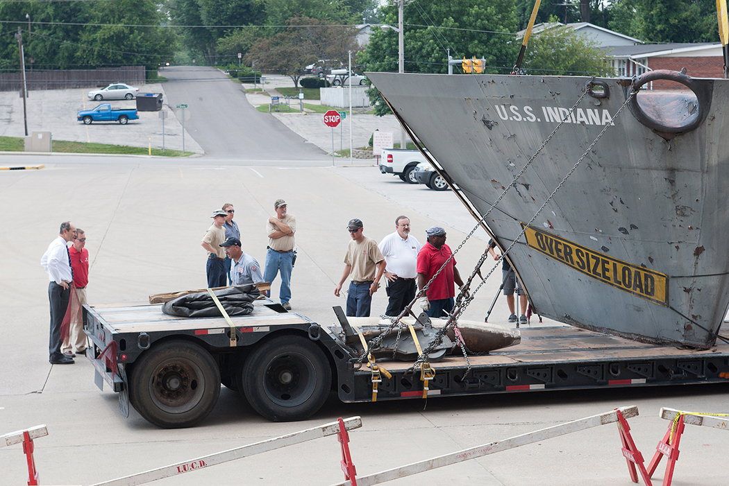 "Bearing an ""OVERSIZE LOAD"" sign, the prow of the USS Indiana arrives at Memorial Stadium on a flatbed truck."