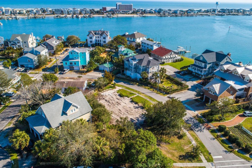An overhead shot of several large houses next to a harbor.