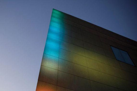 Multicolored lights shine on an angular stone facade that juts into the sky.