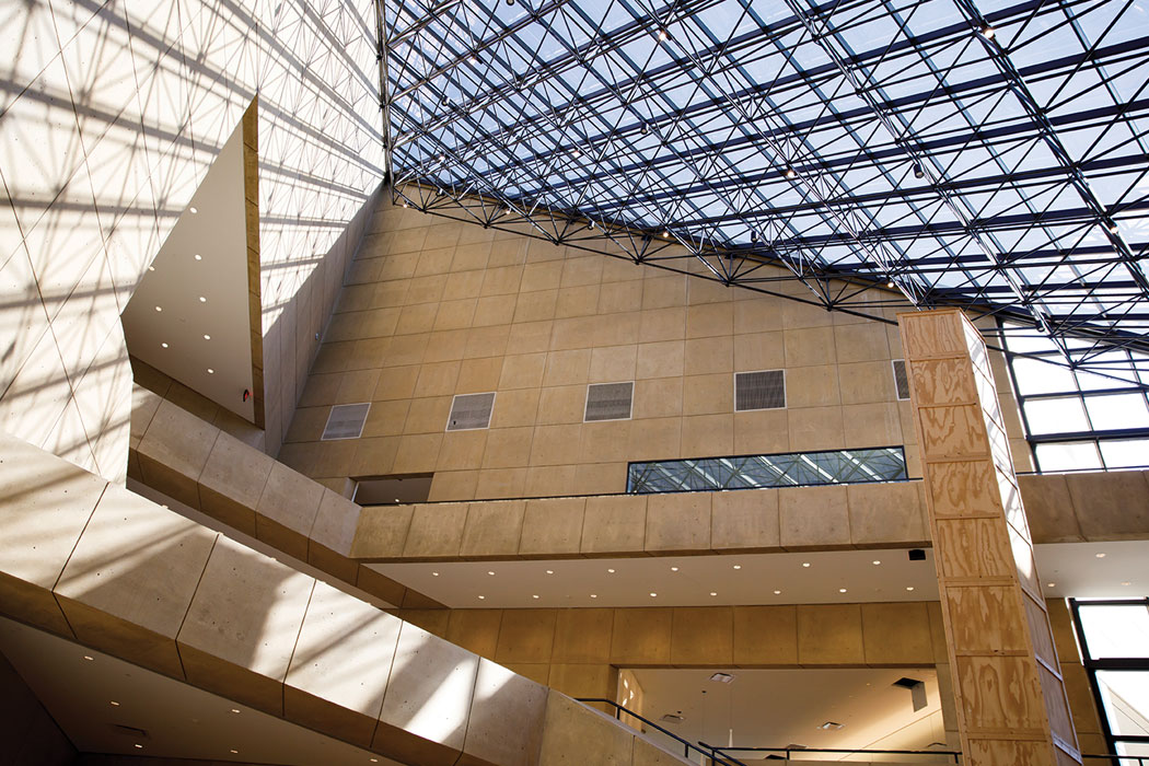 Light shines through a ceiling of windows into an angular, stone-surfaced atrium.